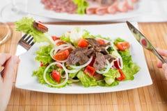 Plantaardige salade met rundvleesvlees en handen met vork Stock Afbeelding