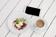 Plantaardige salade, onmiddellijke koffie in kop en smartphone op wit houten bureau royalty-vrije stock afbeelding