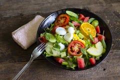 Plantaardige salade op een zwart van het het verliesconcept van het plaatgewicht Gezond voedsel stock fotografie