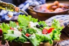 Plantaardige slasalade Olijfolie het gieten in kom salade Italiaanse mediterrane of Griekse keuken Vegetarisch veganistvoedsel stock afbeeldingen