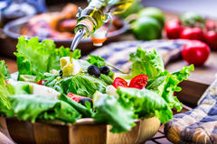 Plantaardige slasalade Olijfolie het gieten in kom salade Italiaanse mediterrane of Griekse keuken Vegetarisch veganistvoedsel