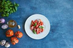 Plantaardige tomatensalade met extra eerste persing, purpere ui, purper knoflook en basilicum Begeleid door een fles van extra ma stock afbeeldingen