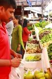 Plantaardige verkoper bij nachtmarkt in Singapore Stock Foto's