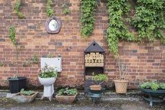 Plantador del jardín del retrete contra una pared de ladrillo imágenes de archivo libres de regalías