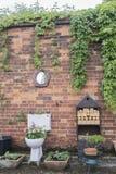 Plantador del jardín del retrete contra una pared de ladrillo foto de archivo