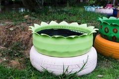 Plantadores verdes coloridos feitos dos pneus reciclados imagem de stock