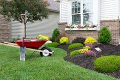 Plantando um jardim do celosia em torno de uma casa Foto de Stock
