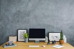 Plantas, cartazes e computador de secretária na mesa no escritório domiciliário cinzento imagem de stock