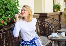 Plantas como decoración natural La muchacha sienta el aroma de las flores de la aspiración del café La mujer sienta la terraza de foto de archivo libre de regalías