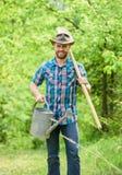 Plantas crescentes Chapéu de vaqueiro maduro do indivíduo com lata molhando e pá Dia de mandril Plantando ?rvores Compromisso e fotografia de stock royalty free