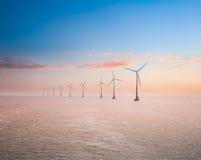 Plantas de energias eólicas a pouca distância do mar no por do sol Imagens de Stock
