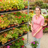 Plantas de las compras de la mujer del centro de jardín Foto de archivo