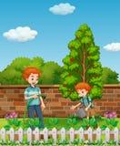 Plantas de riego del padre y del hijo en el jardín Foto de archivo libre de regalías