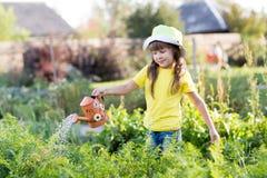 Plantas de riego de la muchacha del niño en un jardín fotos de archivo libres de regalías