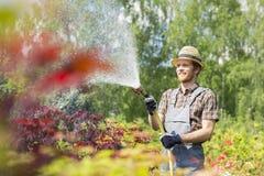 Plantas de riego sonrientes del hombre en el jardín Imagenes de archivo