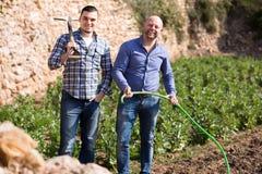 Plantas molhando dos fazendeiros felizes imagens de stock