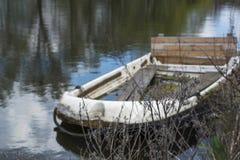 Plantas secas con el barco muy viejo en el agua tranquila en la luz del día como fondo Imagen de archivo libre de regalías