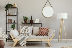 Plantas verdes en potes, velas y libros en estantes del metal en sala de estar escandinava beige fotos de archivo