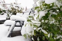 Plantas y sillas de jardín debajo de la nieve profunda Foto de archivo