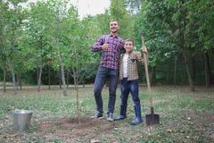 Plantation d'un arbre généalogique Jeune homme heureux plantant un arbre tandis que son petit frère l'aidant Jour de terre Nous f Image stock