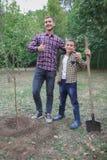 Plantation d'un arbre généalogique Jeune homme heureux plantant un arbre tandis que son petit frère l'aidant Jour de terre Nous f Photographie stock libre de droits