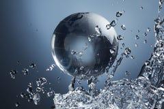 Planète en verre de globe dans l'éclaboussure de l'eau de baisse sur le bleu Photos stock