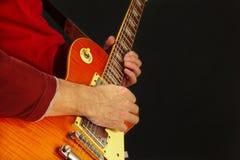 Planteamiento de las manos del artista que toca la guitarra eléctrica en fondo oscuro Imagen de archivo
