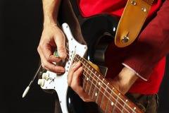 Planteamiento de las manos del guitarrista de la roca que tocan la guitarra eléctrica en fondo negro Foto de archivo libre de regalías