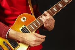 Planteamiento de las manos del músico de la roca que toca la guitarra eléctrica en fondo oscuro Imagen de archivo