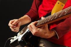 Planteamiento de las manos del músico que tocan la guitarra eléctrica en fondo negro Fotos de archivo