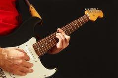 Planteamiento de las manos del músico que tocan la guitarra eléctrica en fondo negro Imágenes de archivo libres de regalías