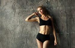 Planteamiento modelo de la aptitud femenina apta y mostrar de su cuerpo muscular con los músculos abdominales fuertes y bronceado imagen de archivo libre de regalías