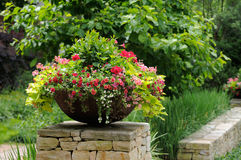 Planter. Metal planter with flower arrangement (million bells, calibrachoa, geranium, sweet potato vine) framing house entrance Royalty Free Stock Photography