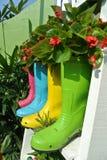 Plantera blommor och grönsaker creatively i gamla plast- kängor Royaltyfria Foton
