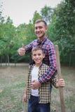 Plantera ett stamträd Lycklig ung man som planterar ett träd medan hans lilla broder som hjälper honom brown räknad dagjord som m Royaltyfri Bild