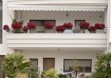 Planters of red begonias on the balcony of a house in Alberobello, Italy. Pictured are multiple planters of red begonias on the balcony of a white house in Royalty Free Stock Photography