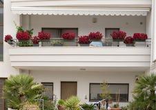 Planteurs des bégonias rouges sur le balcon d'une maison dans Alberobello, Italie Photographie stock libre de droits