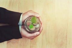 plantez l'élevage avec des pièces de monnaie dans la participation en verre de pot et de main, affaires Images stock