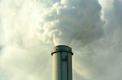 Plantez la fumée de pompage de cheminée dans l'air Photo libre de droits
