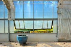 Plantez la maison en verre avec la vue de bassin et de jardin de nénuphar Photo stock