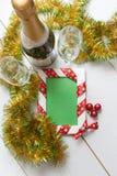 Plantilla de la tarjeta de felicitación hecha de dos vidrios y botellas de champán con las bolas que cuelgan en cinta, la malla y Foto de archivo libre de regalías