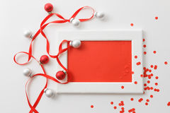 Plantilla de la tarjeta de felicitación hecha del bastidor blanco y de la tarjeta roja con la cinta roja, plata y confeti rojo de Foto de archivo libre de regalías