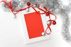 Plantilla de la tarjeta de felicitación hecha del bastidor blanco y de la tarjeta roja con la cinta roja, plata y malla roja del  Foto de archivo libre de regalías