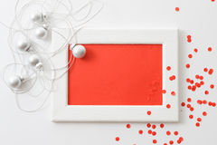 Plantilla de la tarjeta de felicitación hecha del bastidor blanco y de la tarjeta roja con la malla de plata, las bolas y el conf Fotos de archivo libres de regalías