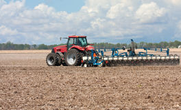 Planting Corn. Farm tractor planting corn in a field Stock Images