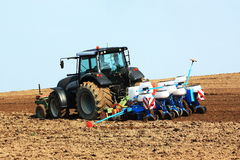 Planting the crop. A farmer uses a tractor with a planting and tillage unit to plant the summer crop in a newly ploughed field royalty free stock photography