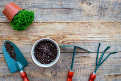 Planting flowers. Gardening tools and pots with soil on wooden background top view copyspace Royalty Free Stock Photo