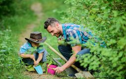 Planting flowers. Little helper in garden. Farm family. Little boy and father in nature background. Gardening tools stock photography