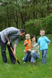 Planting a tree. Father mother and sons planting a tree - working together stock photos