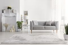 Free Plants And Carpet In White Living Room Interior With Candles Next To Grey Couch. Real Photo Stock Images - 130360594